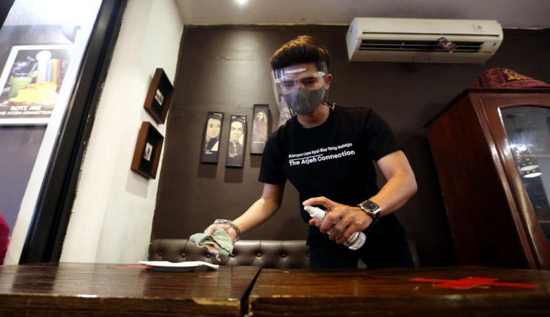 Pelayan membersihkan meja makan di restoran The Aceh Connection, Bendungan Hilir, Jakarta, Selasa (31/8). Pemerintah melakukan sejumlah penyesuaian dalam Pemberlakuan Pembatasan Kegiatan Masyarakat (PPKM) di Jawa-Bali selama sepekan ke depan atau tepatnya dari 31 Agustus hingga 6 September 2021, dengan mengizinkan 1.000 restoran di ruang tertutup beroperasi di beberapa kota. Foto: Ricardo - JPNN.com