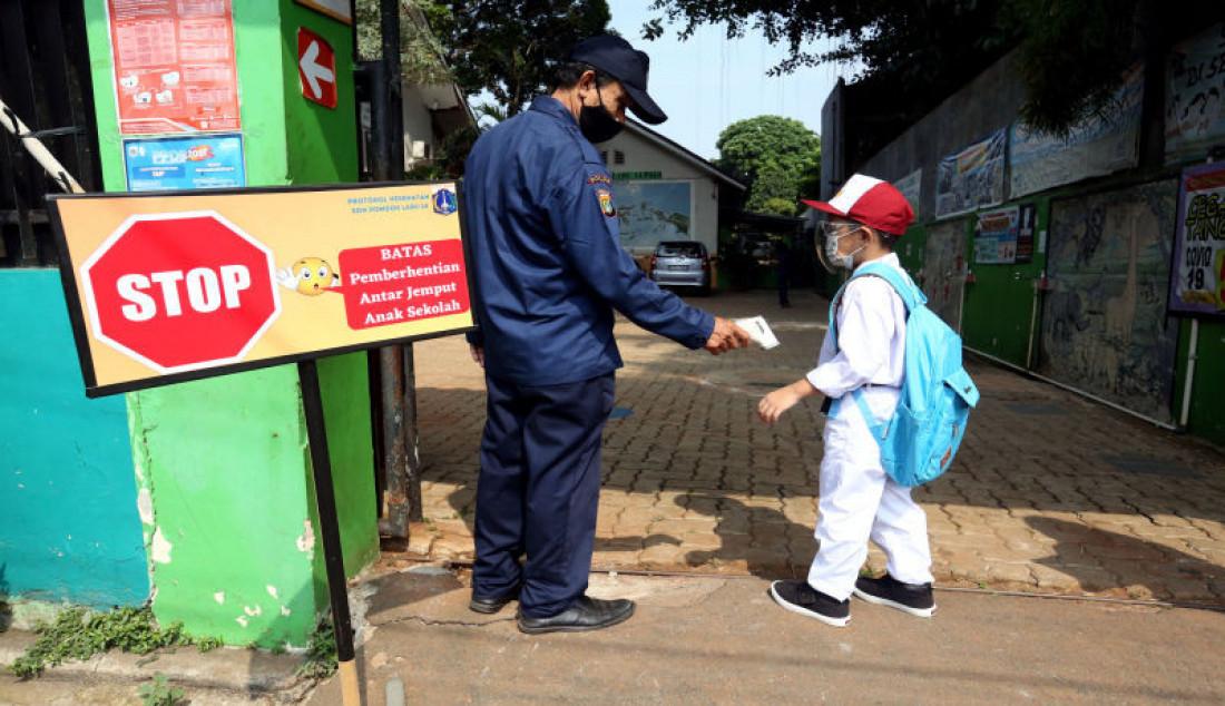 Penjaga sekolah memeriksa suhu tubuh siswa mengikuti pembelajaran tatap muka di SDN Pondok Labu 14 Pagi, Jakarta Selatan, Senin (30/8). Sebanyak 610 sekolah di Ibu Kota menggelar pembelajaran tatap muka secara terbatas dengan protokol kesehatan ketat. Foto: Ricardo - JPNN.com