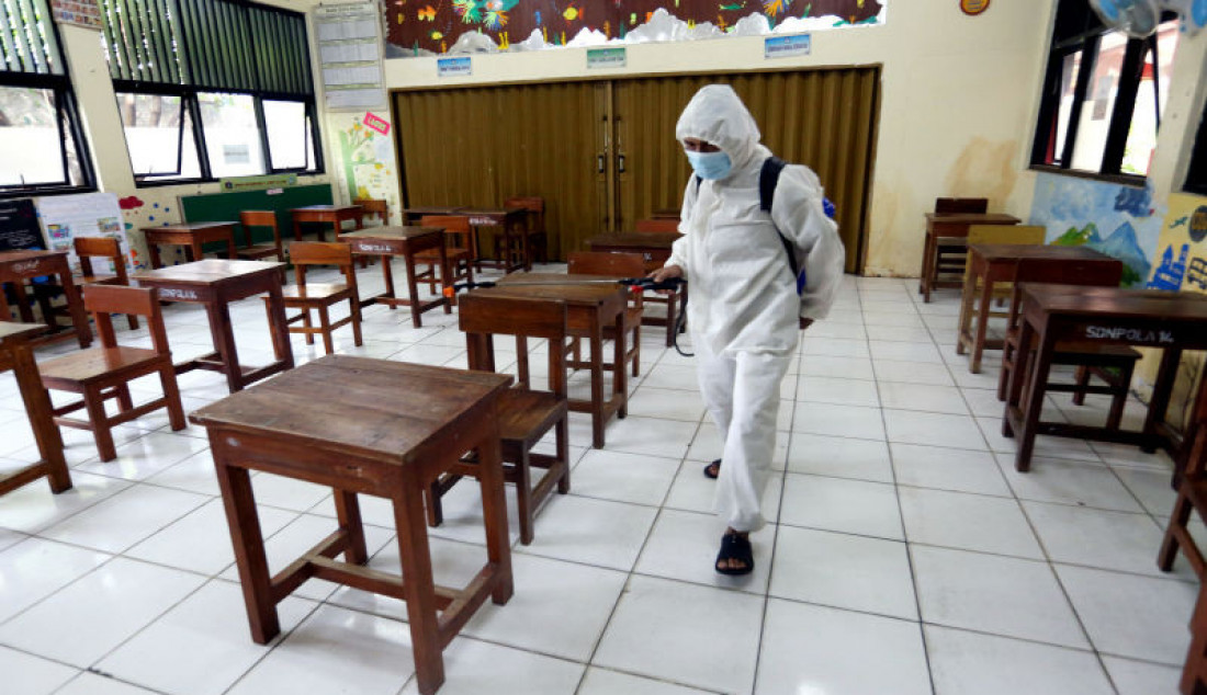 Petugas menyemprotkan cairan disinfektan sebelum dimulai pembelajaran tatap muka di SDN Pondok Labu 14 Pagi, Jakarta Selatan, Senin (30/8). Sebanyak 610 sekolah di Ibu Kota menggelar pembelajaran tatap muka secara terbatas dengan protokol kesehatan ketat. Foto: Ricardo - JPNN.com