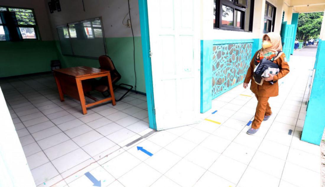 Seorang guru saat memasuki kelas di SMP N 11, Tangerang Selatan, Banten, Senin (6/9).Pemerintah Kota Tangerang Selatan mengizinkan 168 SMP untuk memulai pembelajaran tatap muka (PTM) secara terbatas. Foto: Ricardo - JPNN.com