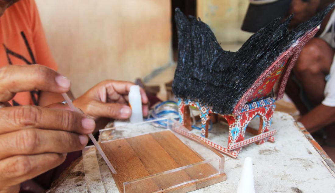 Perajin membuat kerajinan lampu hias berbentuk rumah adat di Mienani Craft, Depok, Jawa Barat, Jumat (17/9). Foto: Ricardo - JPNN.com