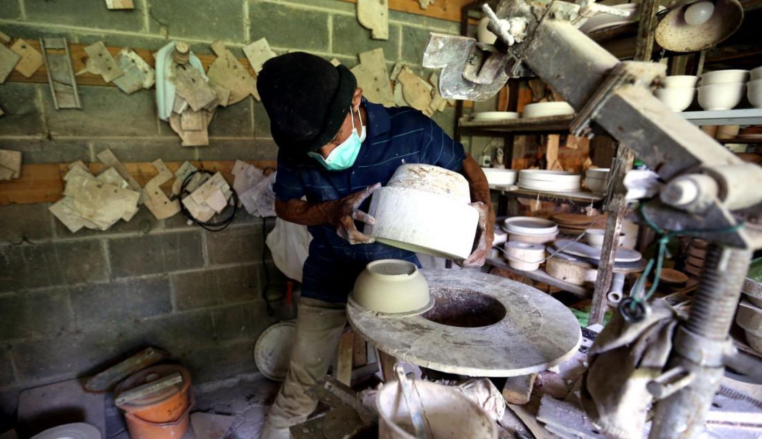Perajin saat mengeluarkan keramik dari cetakan usai dibuat secara handmade di Pekunden Pottery, Bojongsari, Depok, Jawa Barat, Kamis (23/9). Foto: Ricardo - JPNN.com