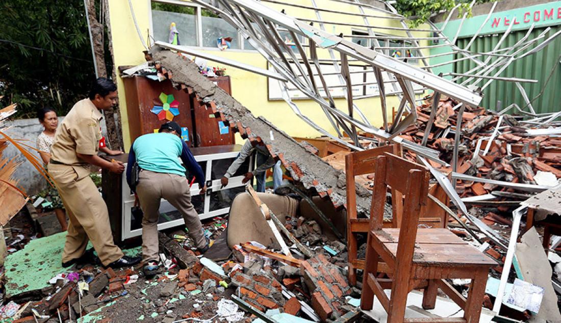 Guru dan pegawai sekolah memindahkan lemari dari reruntuhan atas kelas yang roboh di SDN Cirimekar 2, Cibinong, Bogor, Selasa (6/1). Bangunan sekolah roboh usai diterpa hujan deras. Foto: Ricardo - JPNN.com