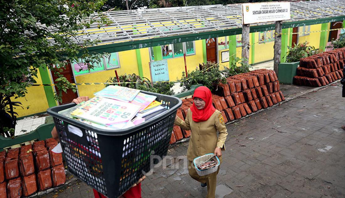 Pegawai sekolah bersama guru melintasi atap ruang kelas yang roboh sambil mengangkut buku bacaan di SDN Cirimekar 2, Cibinong, Bogor, Selasa (6/1). Bangunan sekolah roboh usai diterpa hujan deras. Foto: Ricardo - JPNN.com
