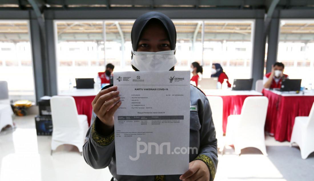 Calon penumpang menunjukkan surat kartu vaksin usai mengikuti vaksinasi vaksin COVID-19 di Stasiun KRL Jakarta Kota, Rabu (28/7). KAI Commuter menambah lokasi vaksinasi di Stasiun Duri, Angke dan Jakarta Kota bagi para penumpang dan warga sekitar stasiun yang dilaksanakan setiap jam 10.00 - 14.00 WIB. Foto: Ricardo - JPNN.com
