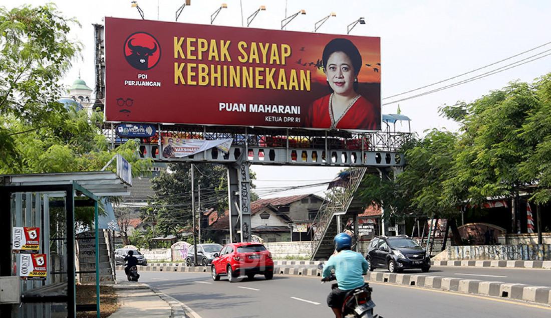 Para pengguna jalan di Jalan Raya Ciputat, Tangerang Selatan, Banten, melintas di bawah bawah baliho bergambar Ketua DPR Puan Maharani, Jumat (30/7). Foto: Ricardo - JPNN.com
