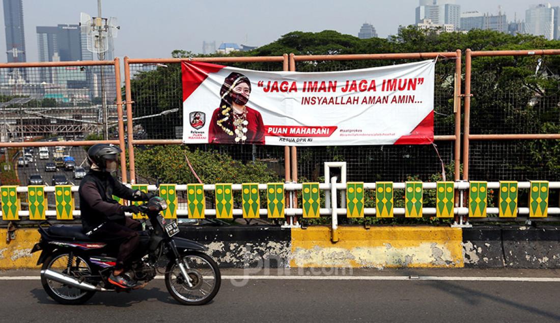 Pengendara sepeda melintas di depan spanduk bergambar Ketua DPR Puan Maharani di Flyover Ladogi, Jalan Jenderal Gatot Subroto, Jakarta Pusat, Jumat (30/7). Foto: Ricardo - JPNN.com
